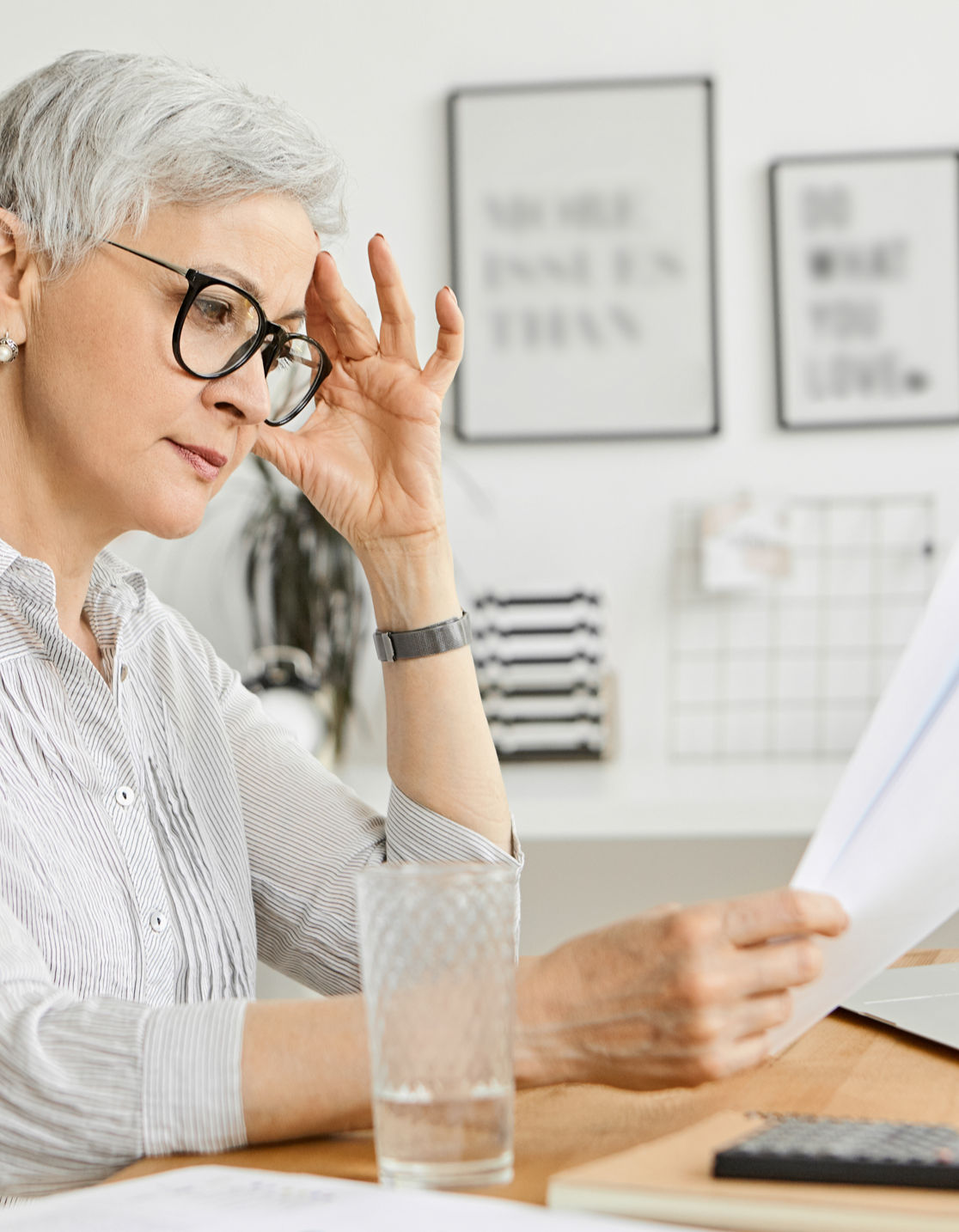 Elderly woman looking at financial documents at a table